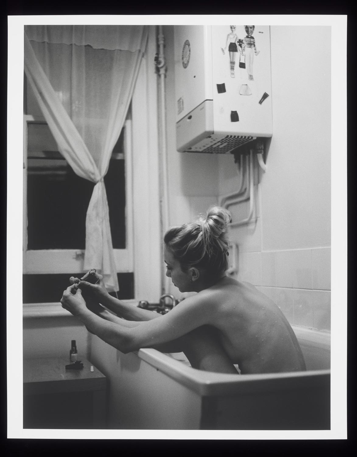 black and white photograph showing woman in a bath holding her foot