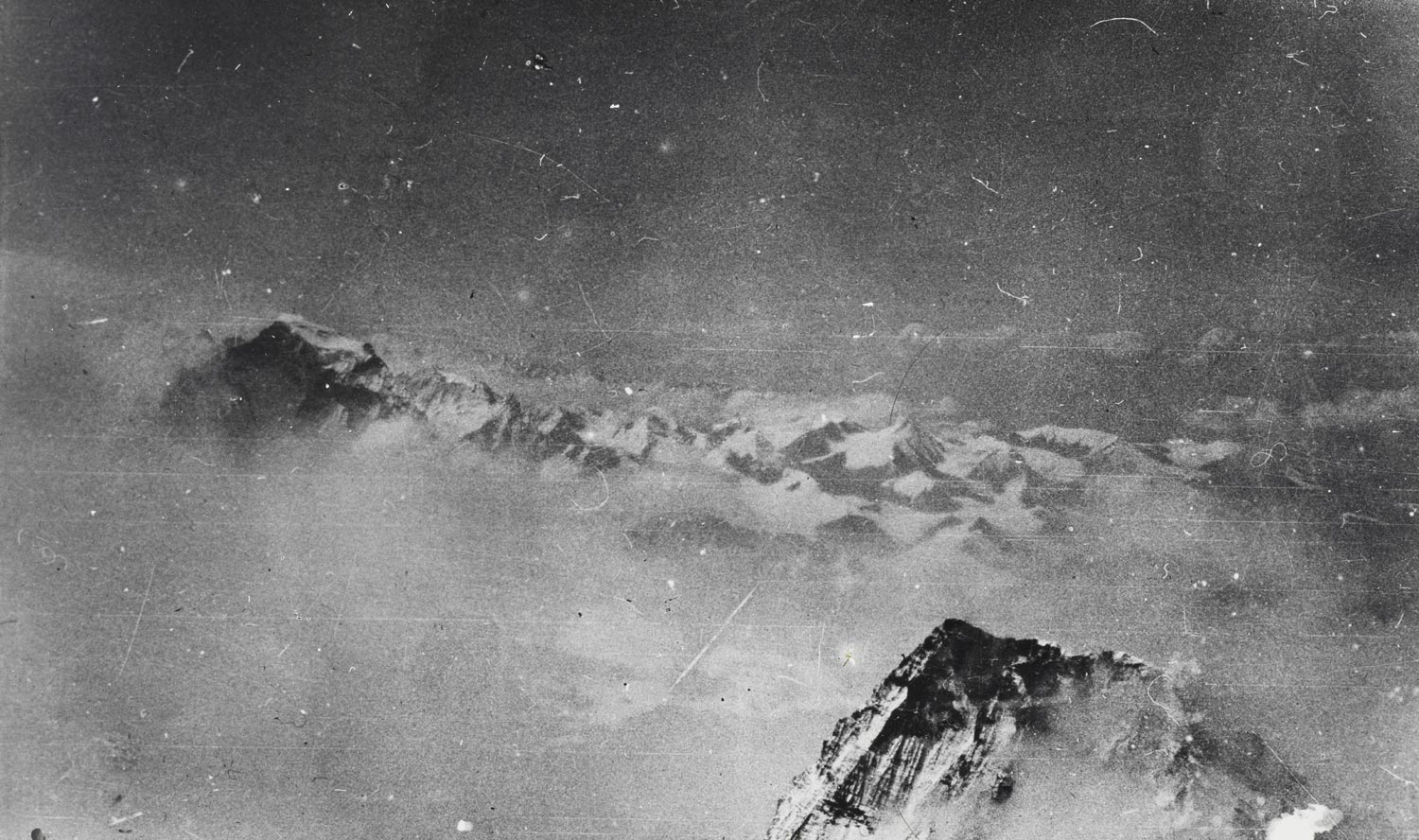 black and white photographic image of mountaintops visible between clouds