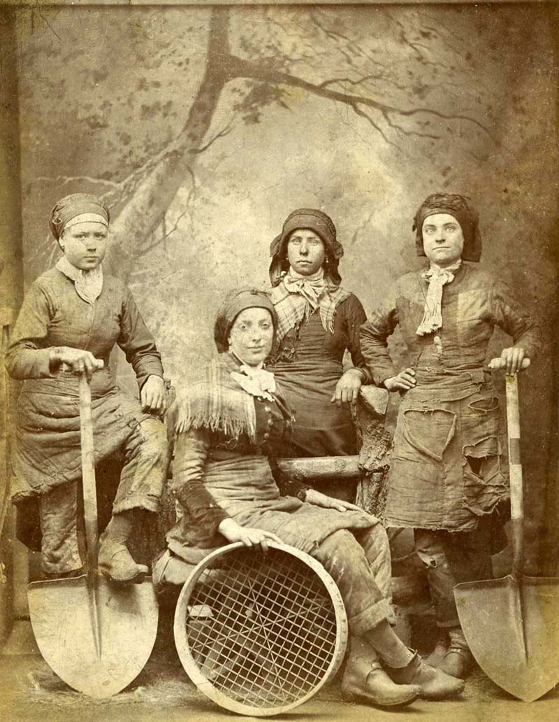 a sepia studio photo of four women in working clothes holding shovels and sifting trays