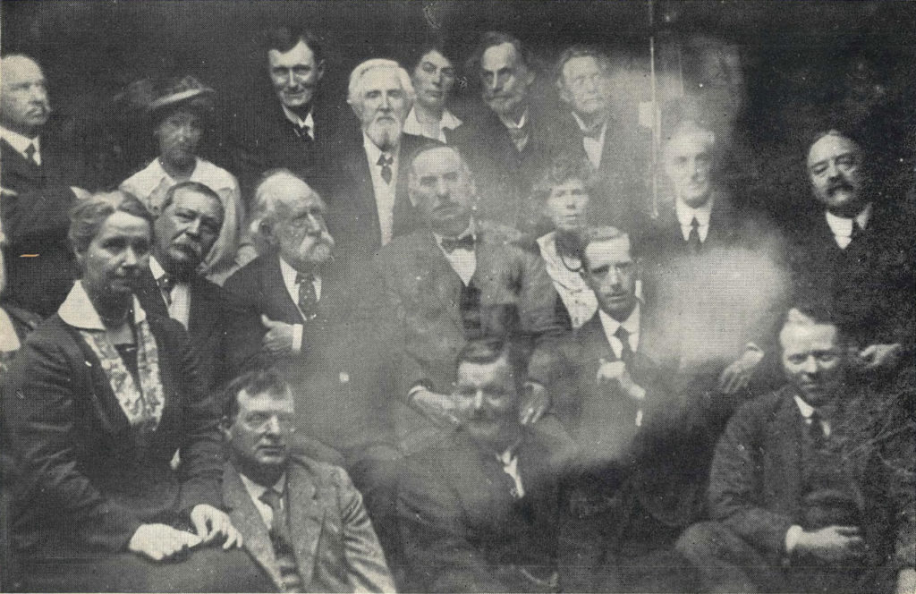 photogrpah of a group of men and women seated. in the centre of the image on its side is the ghostly face of a man
