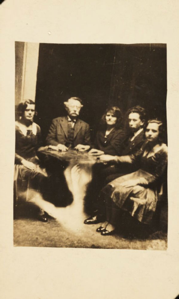 photograph of a group sat at a table attending a seance. A ghostly hand can be seen appearing under the table