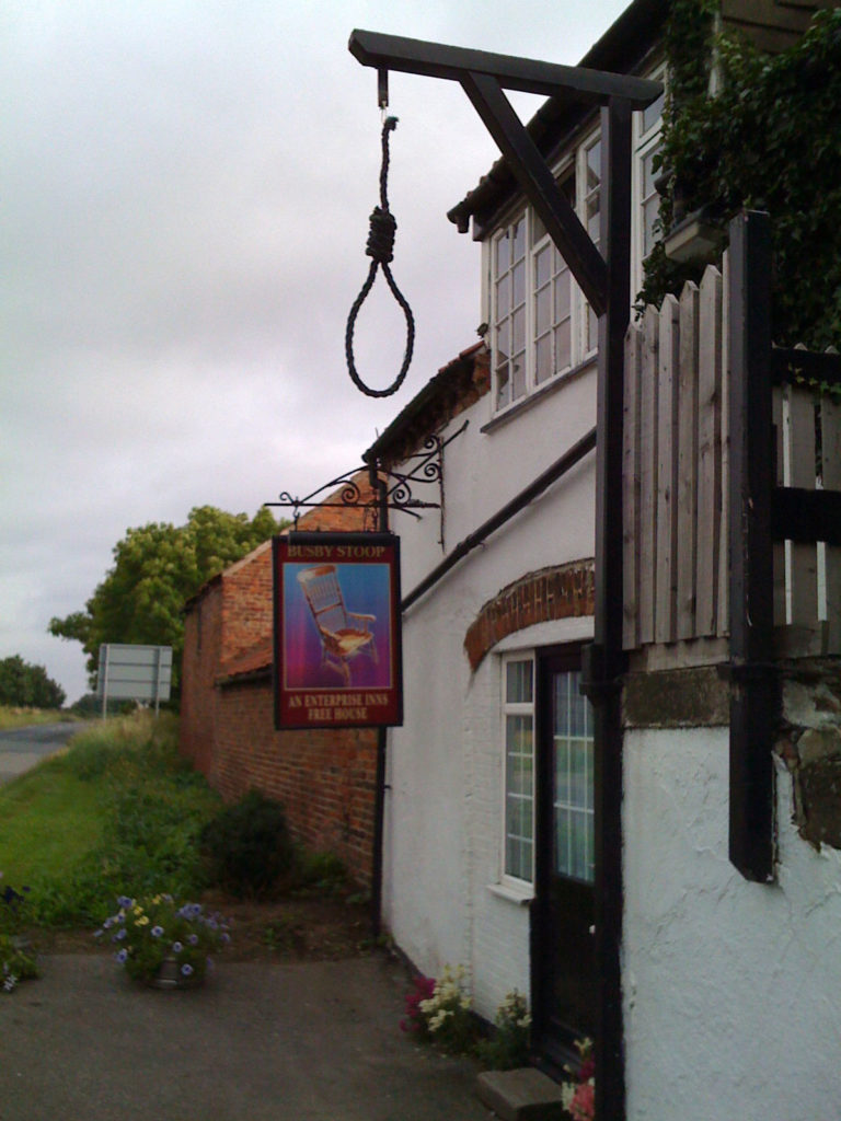 photograph of exterior of pub showing pub sign with painted chair and decorative gallows