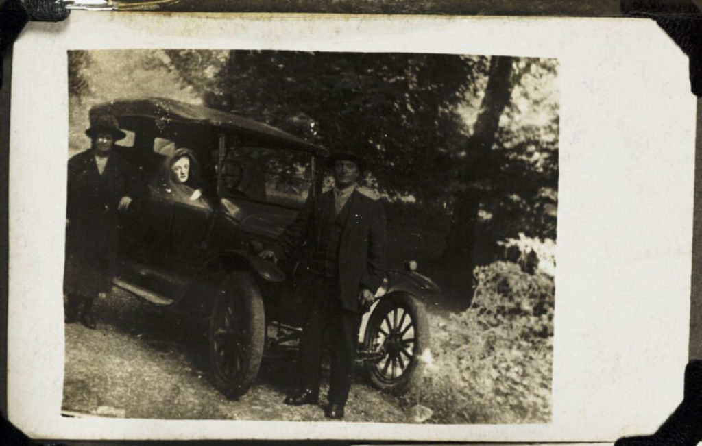 photograph of couple standing outside a car, with a ghostly apparition seated in the vehicle