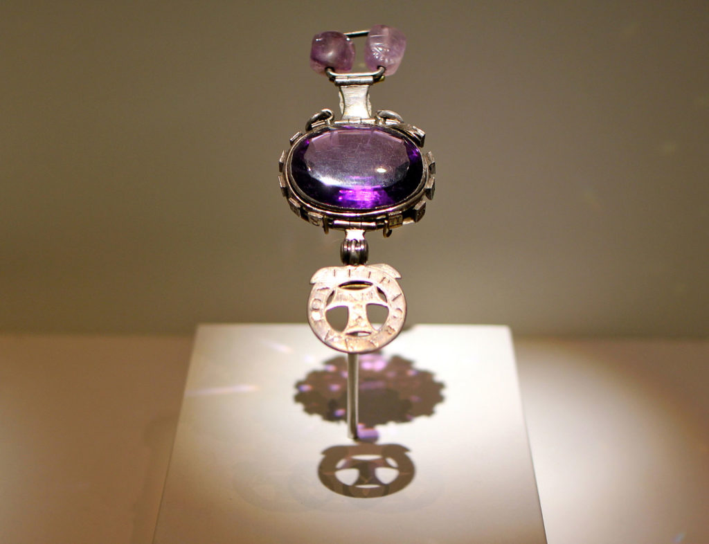 photograph of museum display showing piece of amethyst with metal surround