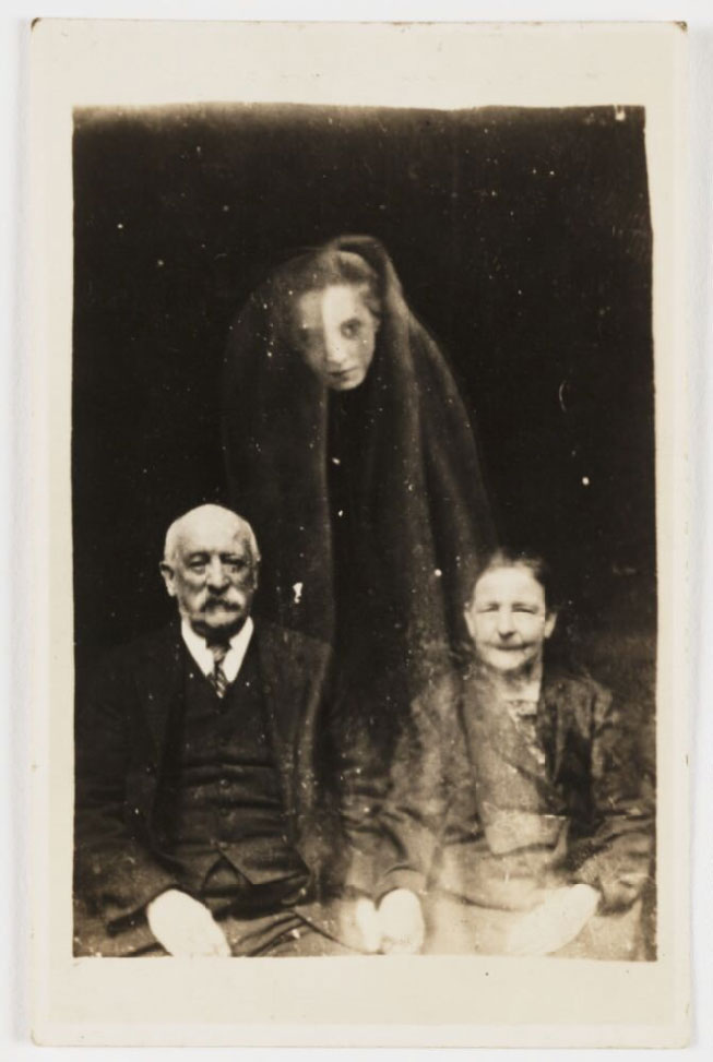 photograph of seated man and woman with ghostly apparition of woman above their heads