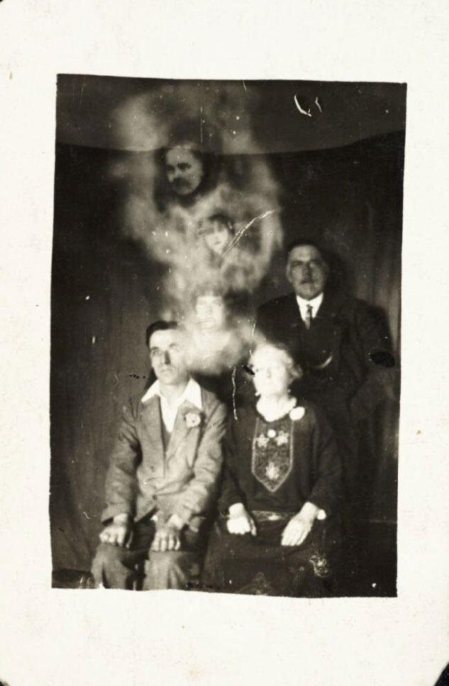 photograph of seated family group showing spirit-like apparitions and faces