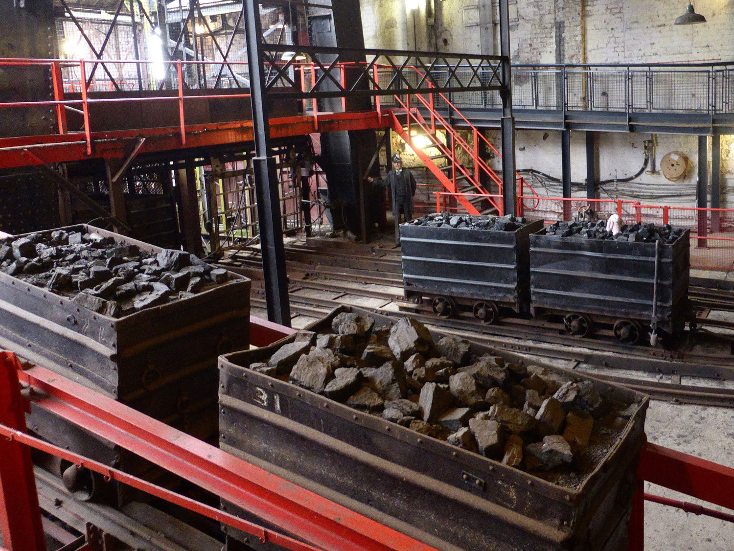 photograph of interior of disused coal mine warehouse showing containers of coal on railway tracks