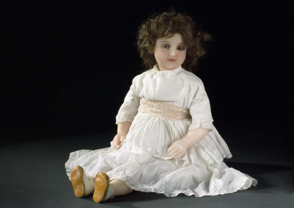 Poured wax doll,with head turned to one side; inset,large vivid blue glass eyes with inserted lashes, well shaped lips, eyebrows and long brown curled wig, on a fabric body with wax lower limbs, in a white lace trimmed gown.
