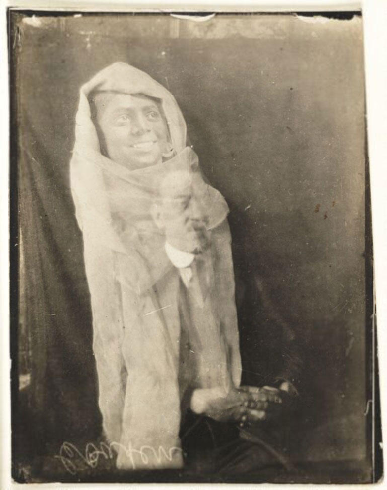 photograph of seated man with the translucent apparition of a man draped in white above his head