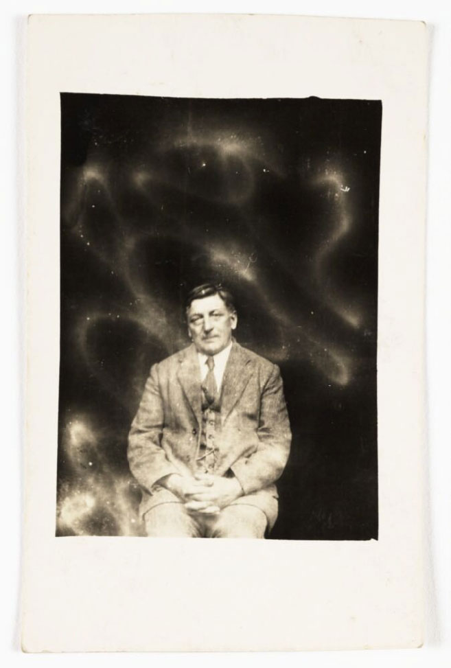photograph of seated man with swirling shapes of light surrounding him