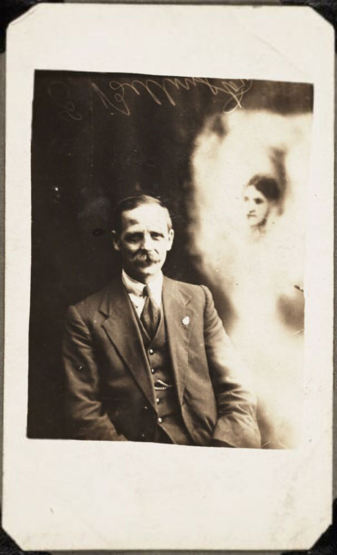 photograph of seated man, with ghostly apparition showing woman's face next to him