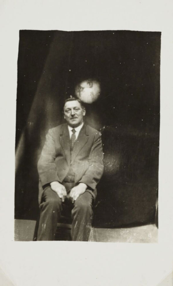 photograph of a seated man, above his head is a circular apparition of another man's face