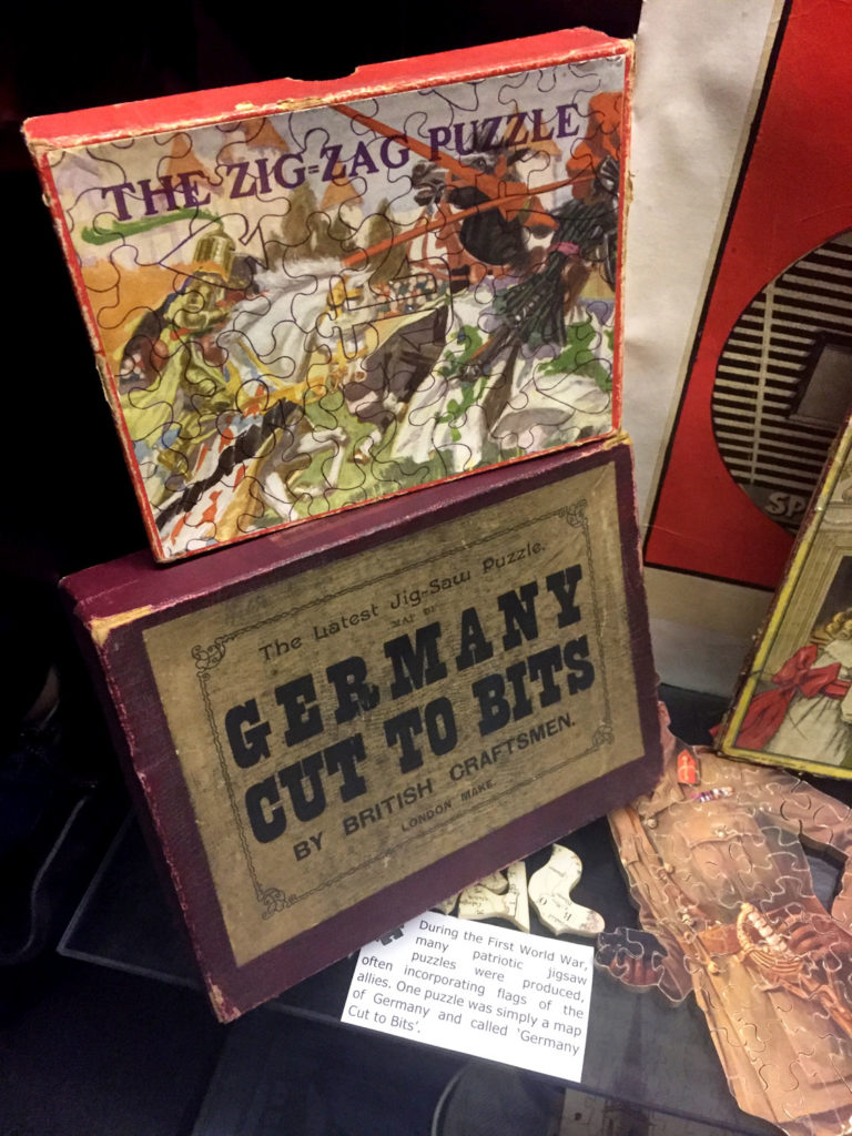 photograph of museum display showing puzzles and puzzle bozes