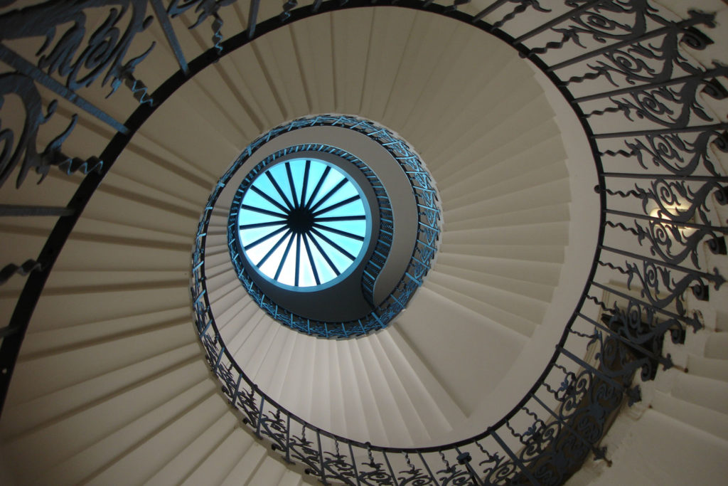 photograph of staircase from below, looking up towards a circular skylight