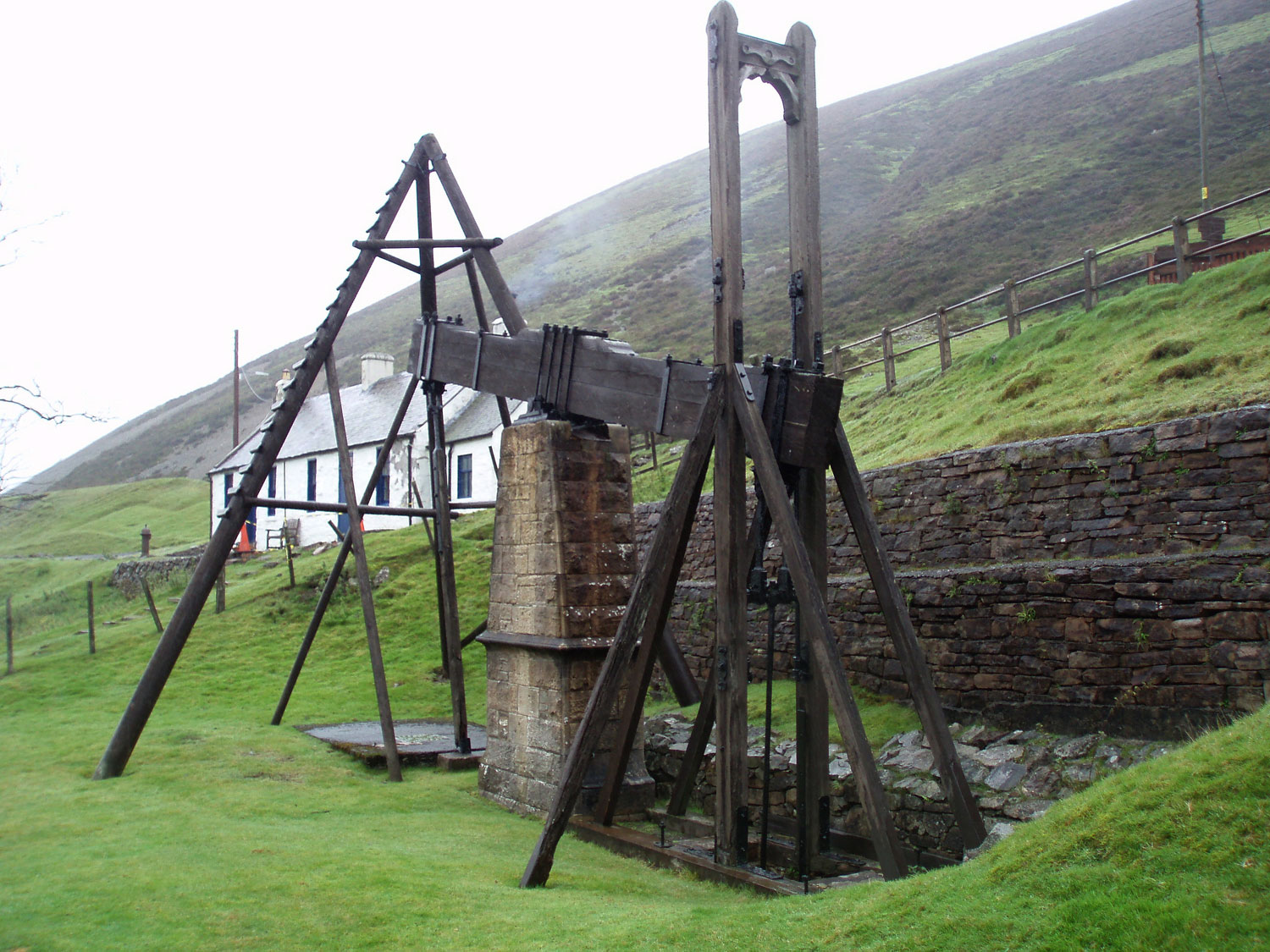 photograph of wooden beam engine in front of small workers cottages