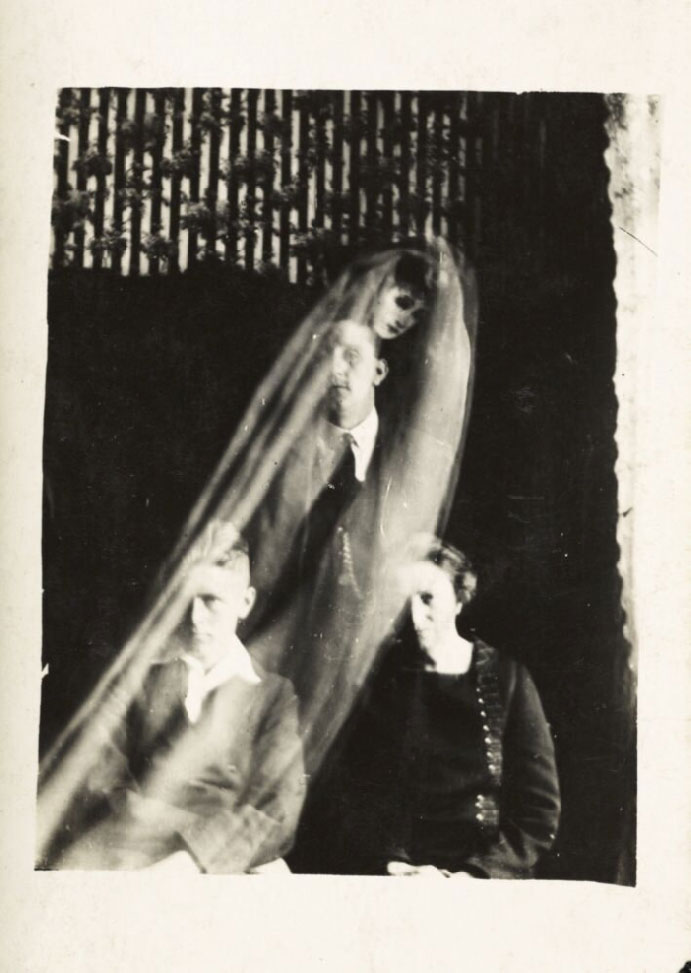 photograph showing portrait of woman and two boys with ghost-like face above one of the boy's head