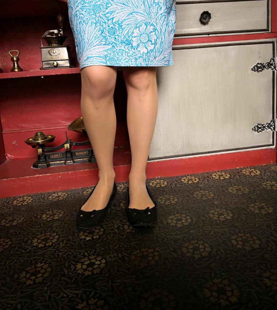 a photo of the legs and skirt of person standing on green, floral patterned lino