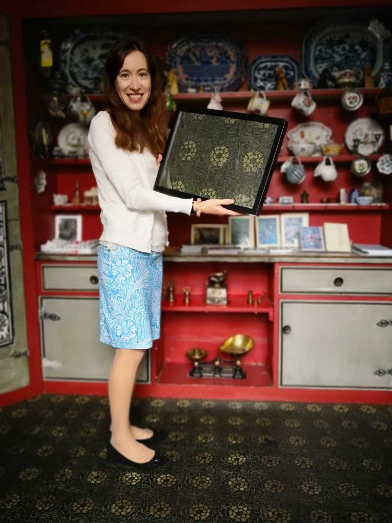 a photo of a women in blue skirt holding a famed print in an old kitchen