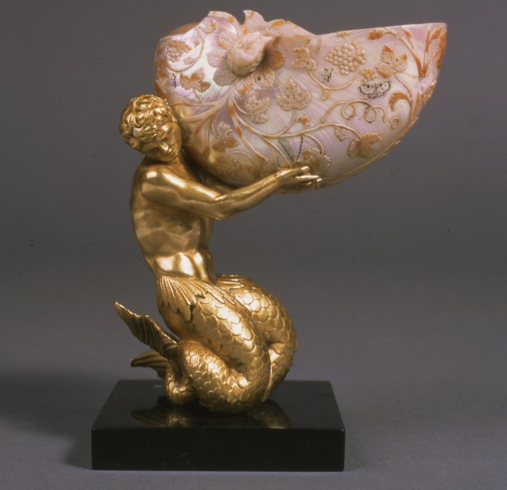 a small desk sculpture of a silver figure holding a decorated shell