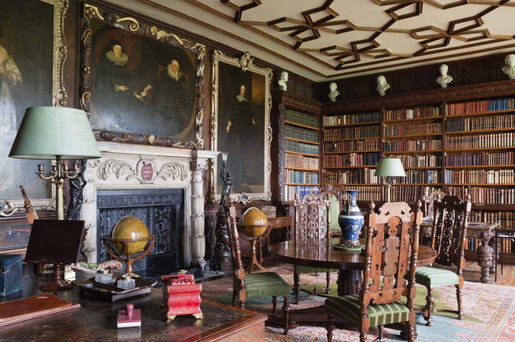 a photo of a panelled room with table in the foreground, fireplace, pictures and lots of books on the walls