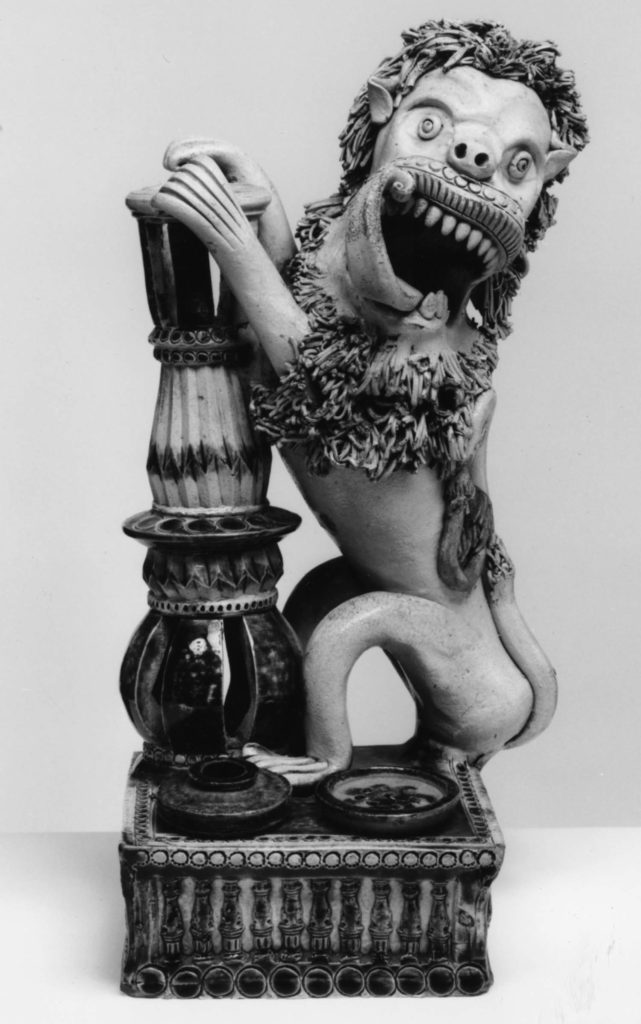 a photo of a porcelain lion rearing up and holding a column