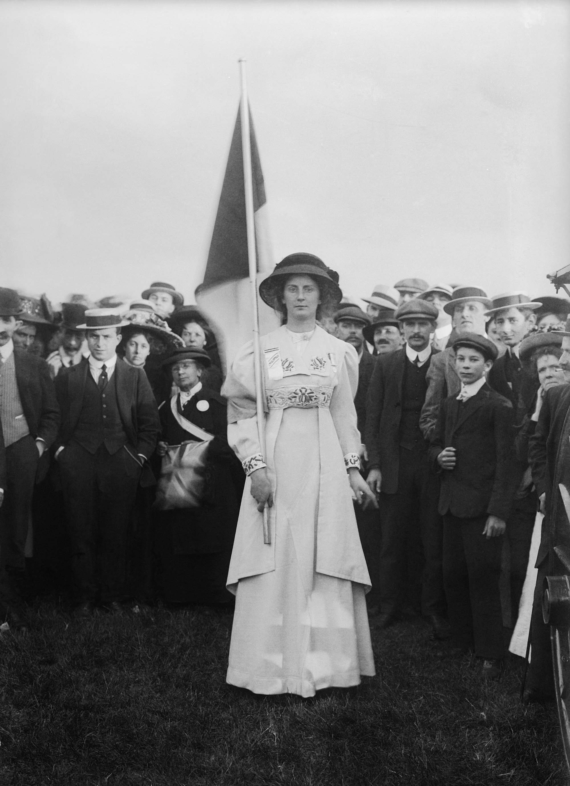 a black and white photo of a proud looking woman standing with a banner as a group of men and women behind her look on