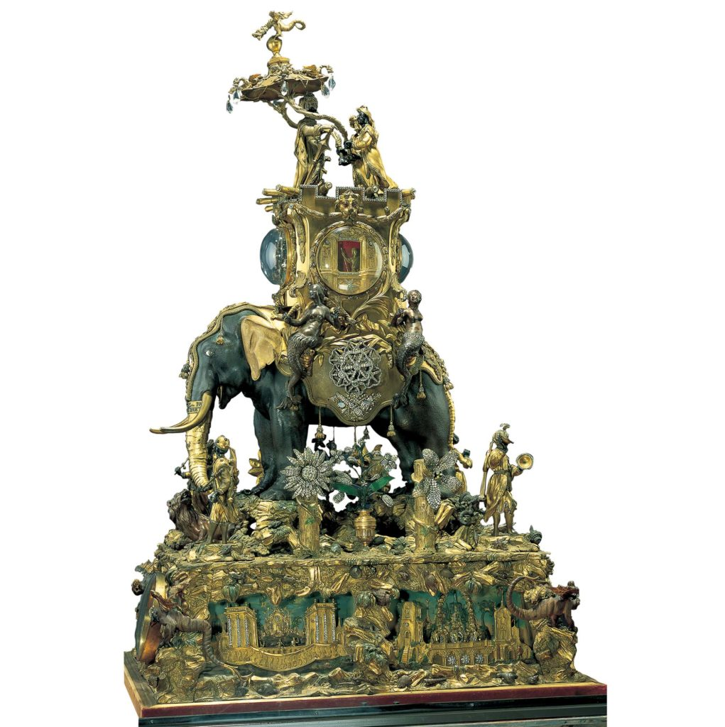 a model of an elephant decorated with gold figures on base of green and gold