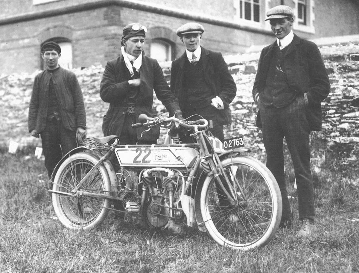 black and white photo of men in flat caps with a man with a motorbike