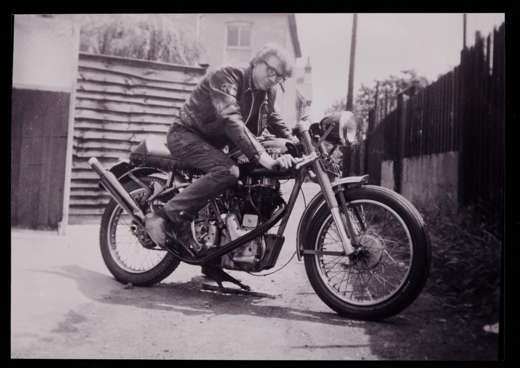 a black and white photo of a man in a leather jacket posing on a motorbike
