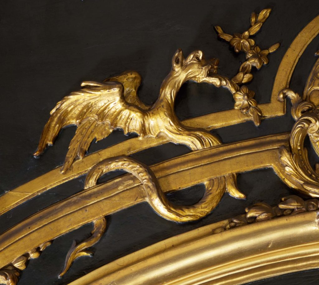 a detail of a dragon decoration in gold on a gilded ceiling decoration