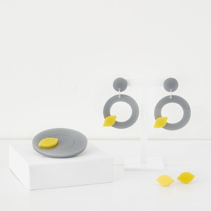 photograph of pair of earrings with grey circles and lemons, pair of lemon stud earrings and brooch with great circle and lemon