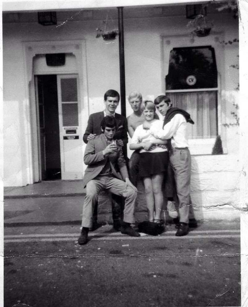 a black and white photo of four male mods and a girl outside a cafe