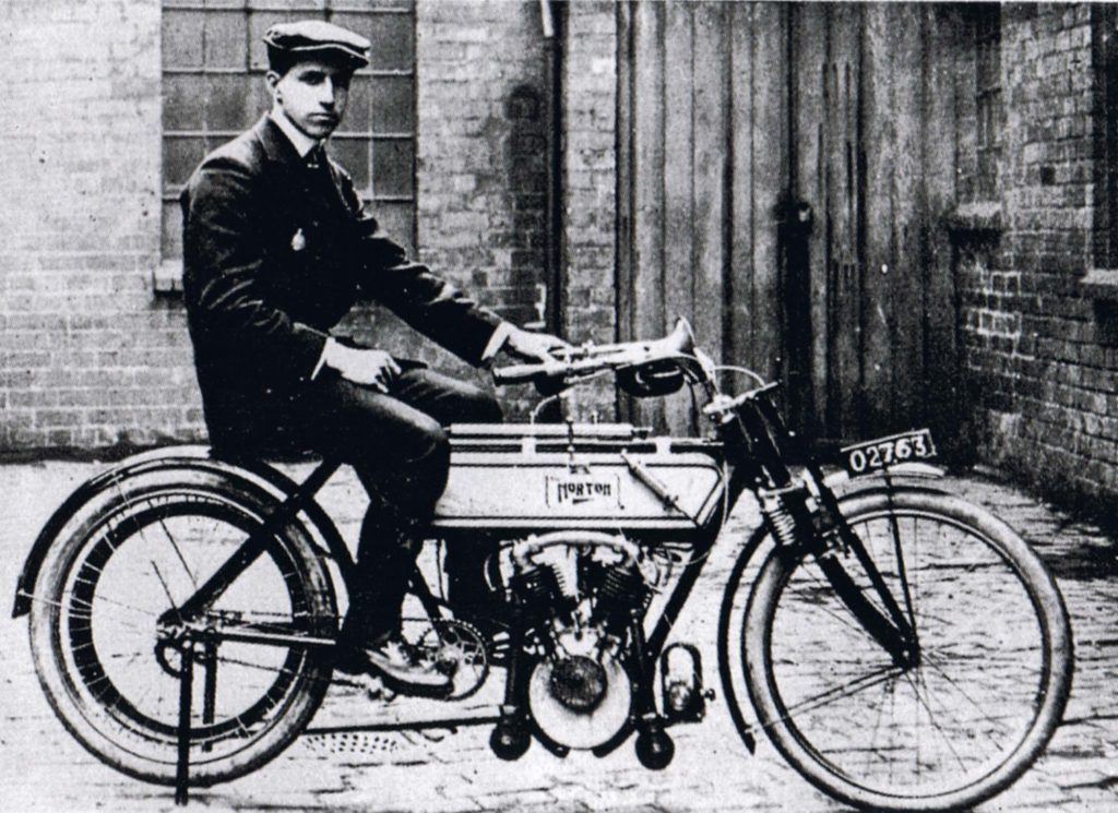 a photo of a man in a flat seated on an old-fashioned motorbike