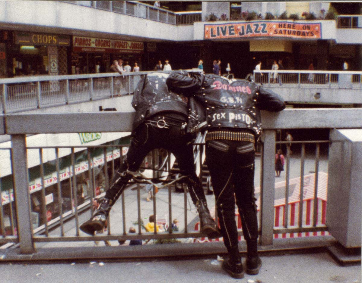 a photo of two people dresses in leather jackets and bondage gear leaning over a balcony in a shopping centre