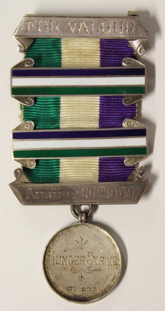 a photo of a medal with a green gold and purple ribbon
