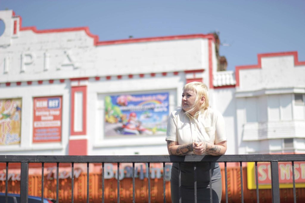 a photo of a girl with white feather cit hair with a fringe leaning across a set of railings with an Art Deco cinema frontage behind her