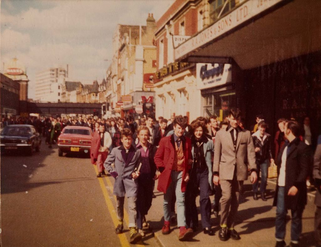 a colour photo of a lot of young men in teddy boy drapes walking down a high street