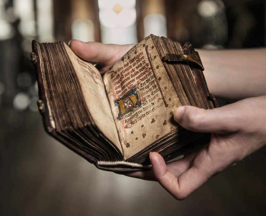 a photo of a pair of hands cradling an open book of hours