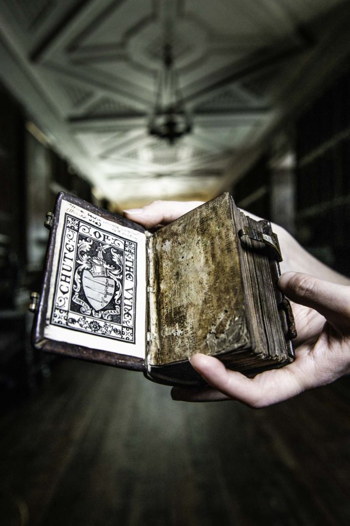 a photo of a pair of hands holding a book in a long gallery