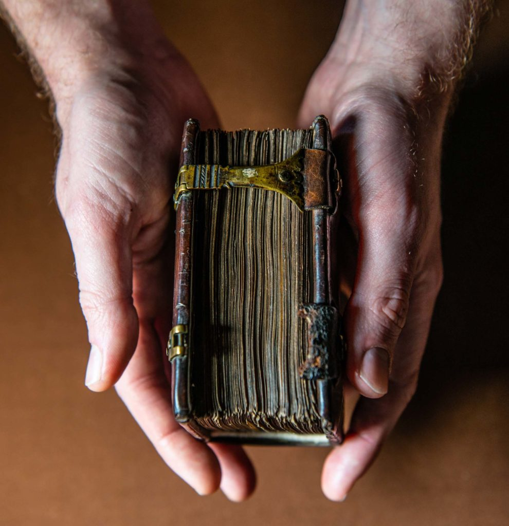 a photo of two hands holding an old book closed together