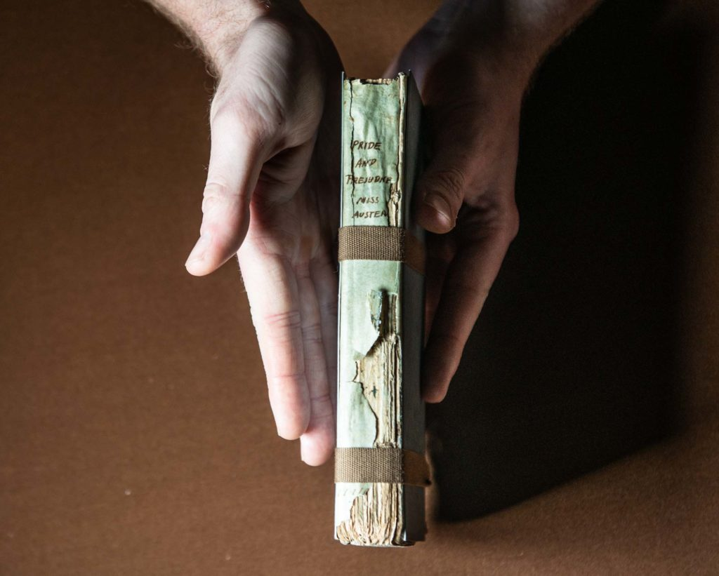 a photo of a air oh hands holding a book a worn book with the spine bearing the title Pride and Prejudice