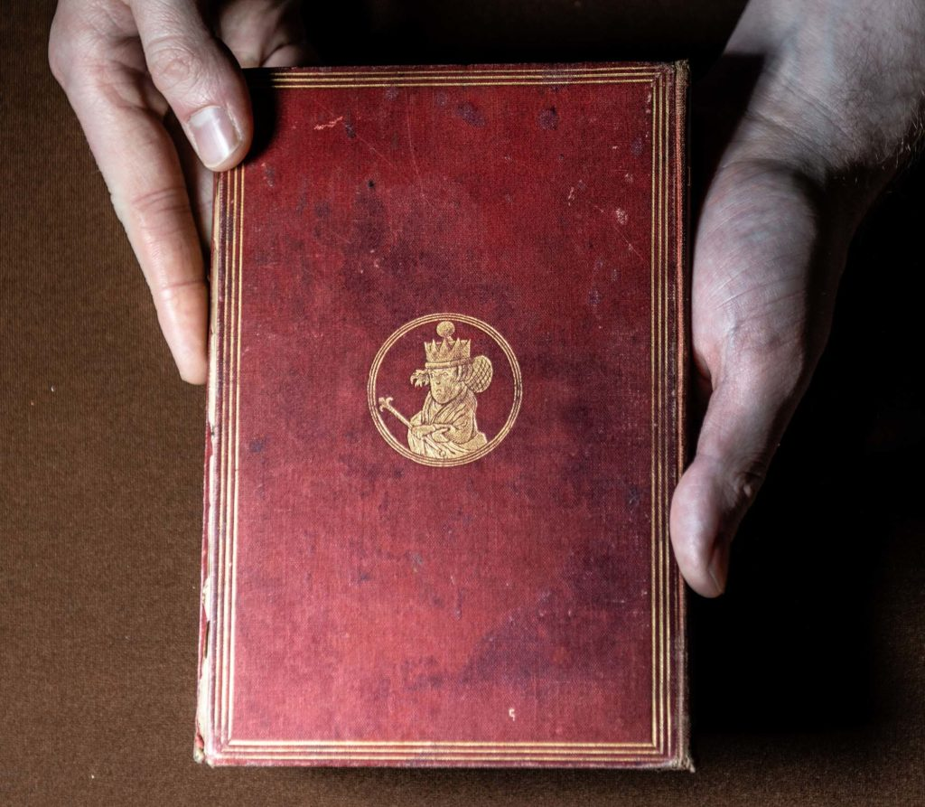 a photo of a pair of hands cradling a book with a red cover