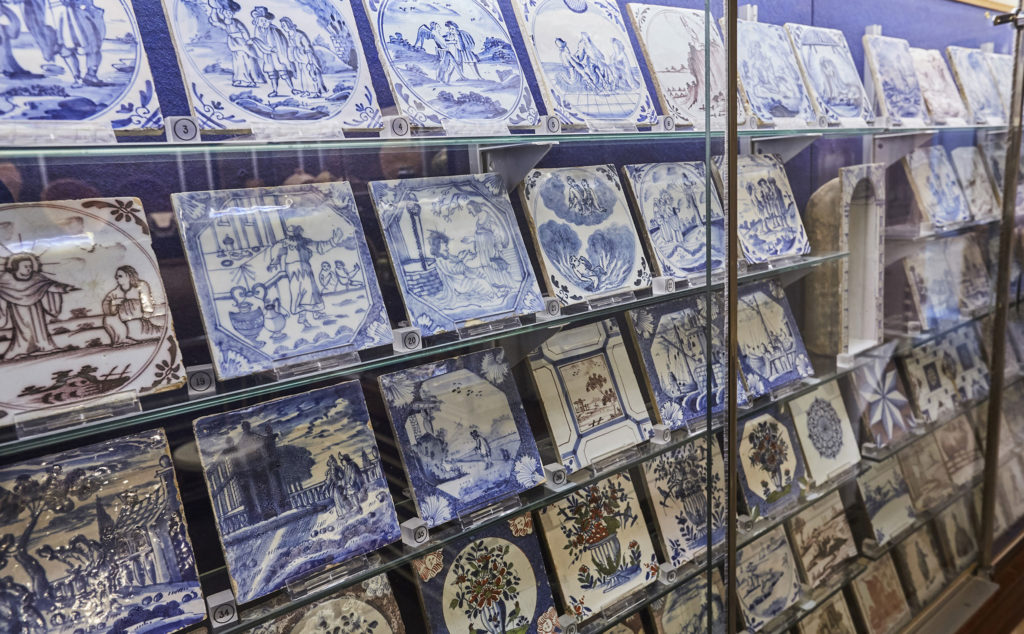 photograph of museum display showing rows of painted tiles in blue and white