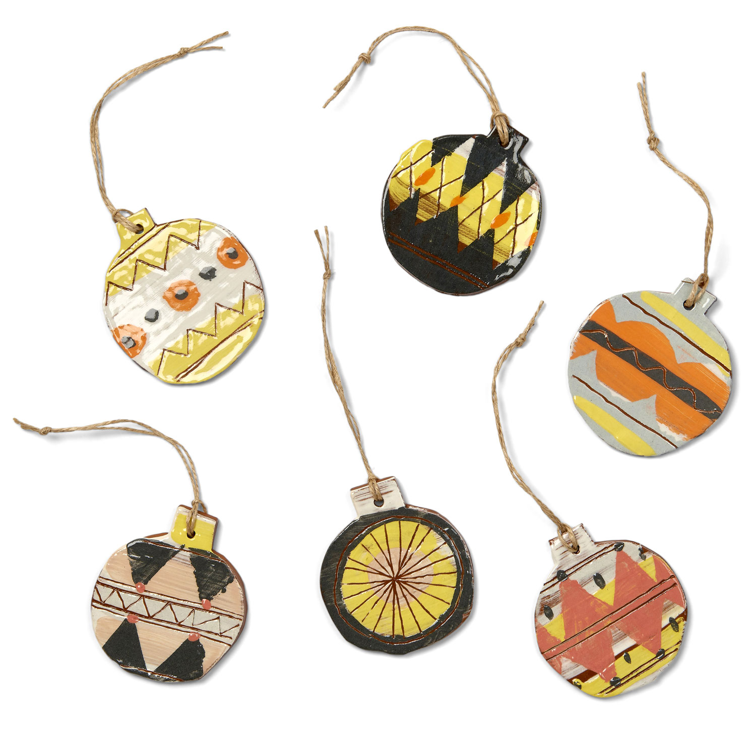 photograph of six ceramic baubles with hand painted designs in orange, yellow, brown and pink