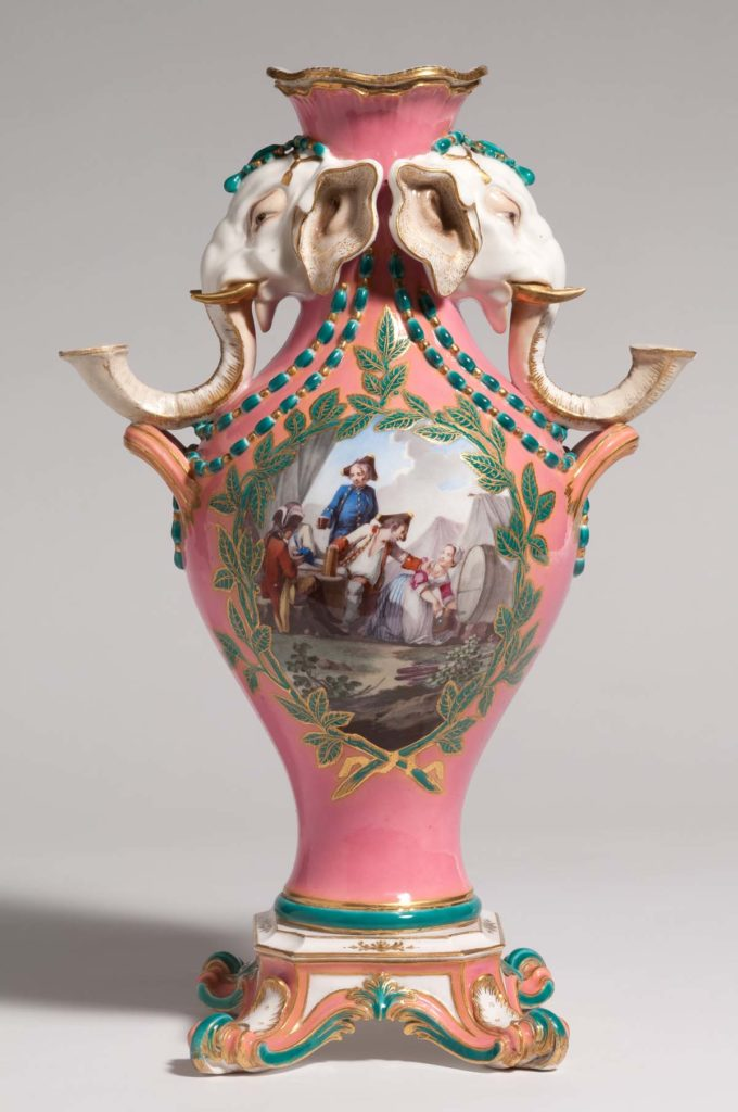 a pink percalin vase with eighteenth century painted figures and two sculpted elephants at the top