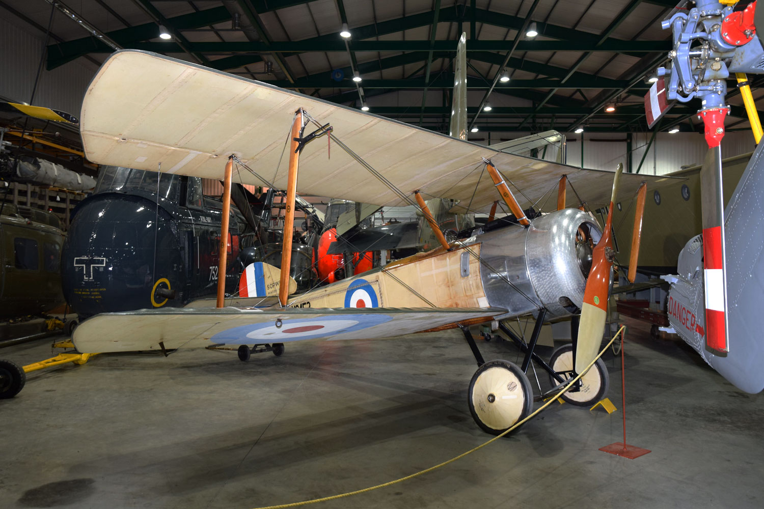 photograph of small military biplane in air hangar surrounded by other aircraft