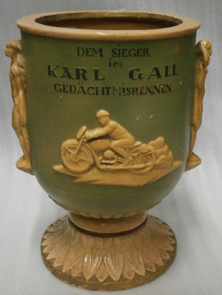 a photo of a green ceramic urn with a motorcycle motif on it