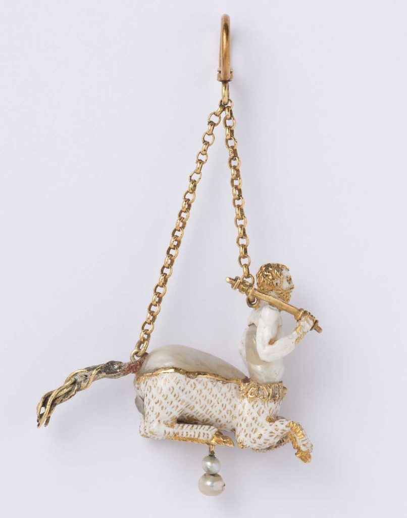a pendant resembling a centaur made from porcelain and gold leaf on a gold chain,
