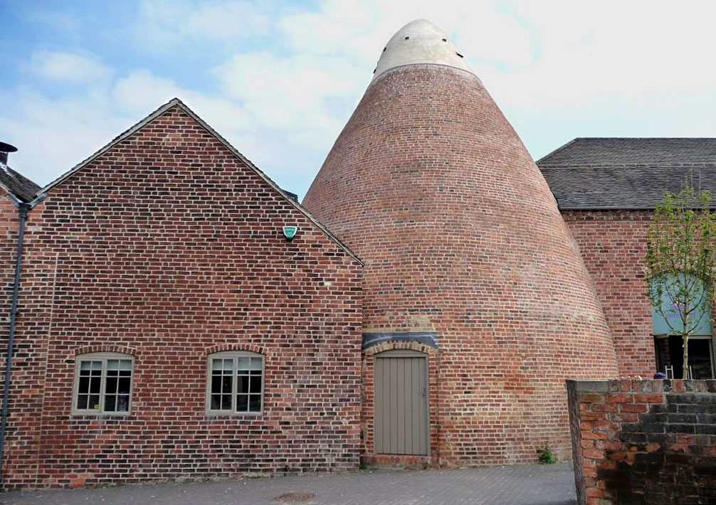 photograph of exterior of pottery works with bottle kiln in centre
