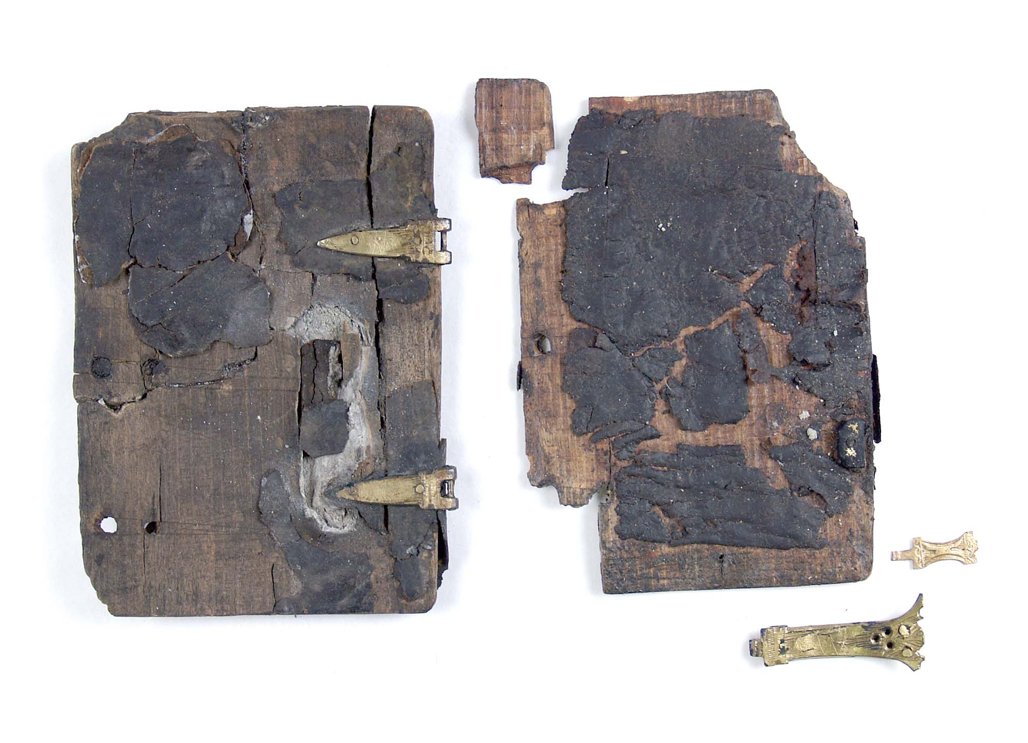a photo of the remains of an old book cover on leather covered wood with metal hinges